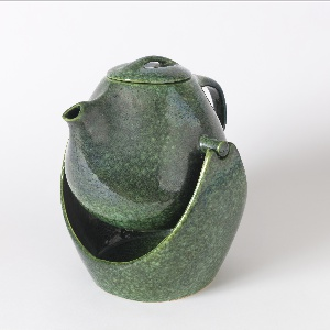 Bulbous coffee pot form with short spout, D-shaped handle and ovoid lid with strap handle; body with molded pegs on either side allowing pot to be suspended in ovoid stand. All in mottled moss green matt glaze.