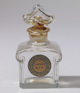 "Bottle (a) of heavy molded, clear glass. Body is oblong in section, with chamfered corners, and with shoulders projecting in a scroll form at narrow sides and marked on the face and reverse as a raised thread spiral. Plain cylindrical neck with a convex ring at angle of base, and a flat, extended rim. Stopper (b) has short concave stem surmounted by a finial, moulded as if formed from a lozenge-in-section; glass rod outlining an inverted heart shape with scrolled ends in center. Circular paper label on front side of body with ""Guerlain, Paris, L'Heure Bleue.""  Box (c) is rectangular, with lid opening from top. Figures and animals top and sides; ""Guerlain"" on lid."