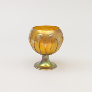 One of a pair of amber vases. Flat base with a flaring stem. Squat bowl with all-around decoration of growing lily plants