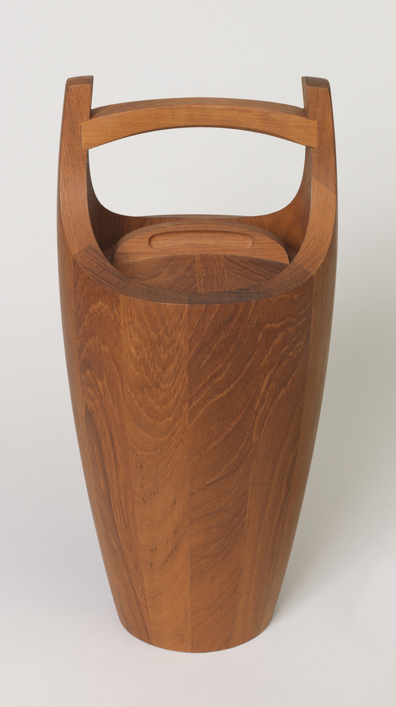 Flaring cylindrical teak-stave form, the sides rising to meet a curved horizontal handle; circular lid with curved handle. Interior with red plastic lining.