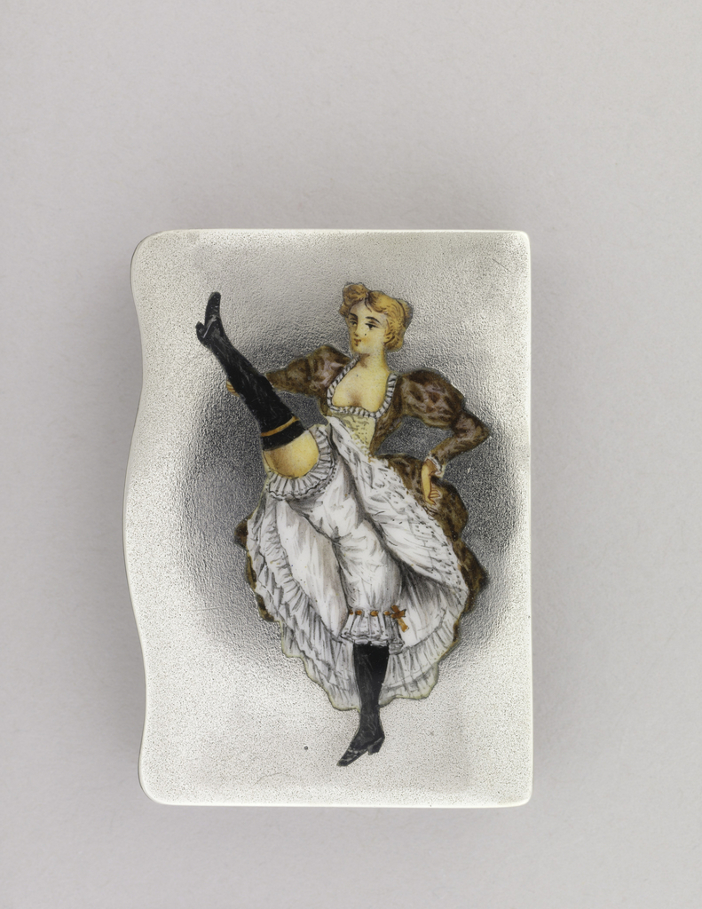 Rectangular, snuff box type container, featuring vertically situated, polychrome enamel image of blond cancan dancer with right leg kicked high. She wears patterned pink dress with low bodice, white petticoats and bloomers, thigh-high black stockings and black shoes. Lid's lip or left edge curved. Lid hinged on right side. Striker on back of same long right side panel.