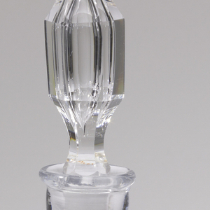 A glass decanter with a finely cut stopper. The decanter has a square body and an etching of a reclining nude on the front.