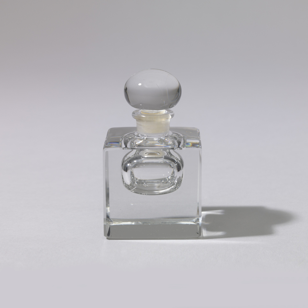 """Cube-shaped, thick, clear glass body with central hollow """"bubble"""" to hold perfume, the edges chamfered on all sides; small tubular neck with rolled lip, acid etched inside; fitted with flattened bubble-shaped stopper of clear glass. Plastic sleeve in plug of stopper."""