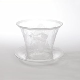 A bowl and stand in glass with a matching pattern around the edges. The flared lip bowl is decorated around the sides with nude women.