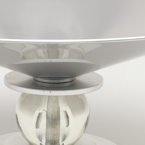 Shallow flared bowl in aluminum. The foot is a rounded plate with a clear glass circle which the bowl sits upon.