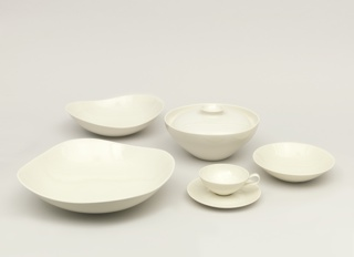 White porcelain round casserole and lid that is nestled within rim of bowl, with flat knob.