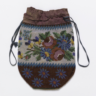 Drawstring pouch with floral patterns. Center band has blue, red and yellow flowers on a white background. Bottom of pouch has blue flowers on a dark red ground. Serrated border separates the bands.