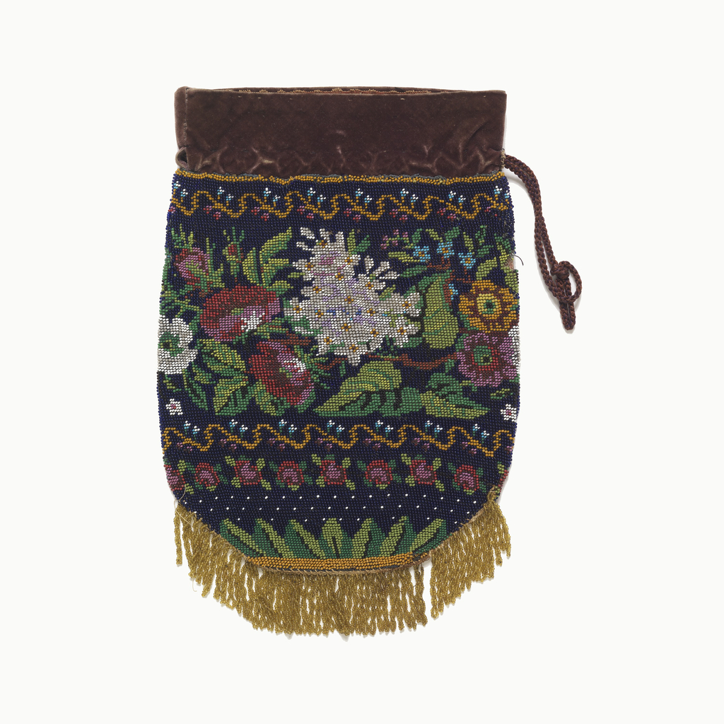 Drawstring bag in beaded knitting, with a wide band of naturalistic flowers framed by narrow borders of stylized floral vine. Gold beaded fringe at bottom; velvet forms drawstring pocket. In dark blue with greens, reds, yellow and white.