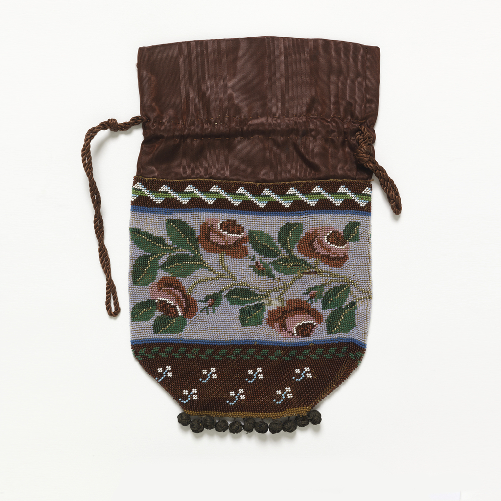 Knitted bag with colored glass beads in design of  a band of red roses on a white ground; brown silk moire at the top with a drawstring of silk cord; metal and silk balls at bottom.