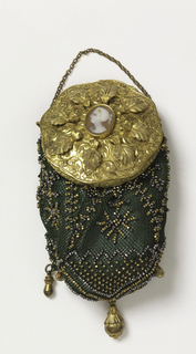 Dark green silk net miser's purse with gilt cut steel beads, mounted on a gold ring with a lid ornamented with a leaf design in relief, and at center, a small cameo of a woman's head in profile. Five gilt drops at bottom.