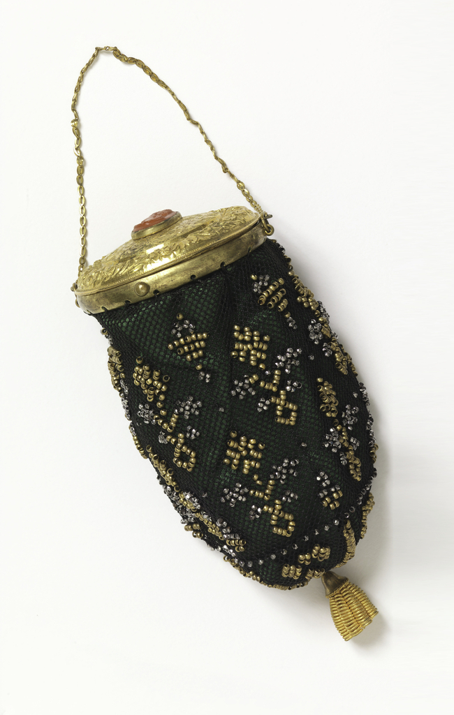 Small sac of crocheted black silk with gilt beads, set within a gold rim with a lid ornamented with a wreath in relief, etched pattern, and a cameo of a head in profile carved in reddish stone. Find gold chain, single gold drop. Lined with green silk.