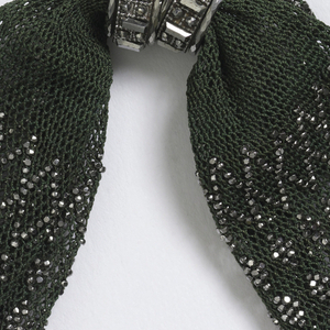 Knotted netting in dark green silk ornamented with cut steel beads in diamond patterns; side opening controlled by two faceted cut steel rings.  Filigreed cut steel drops at each end.