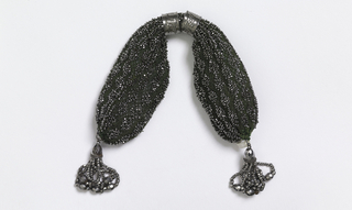 Crocheted dark green silk ornamented with cut steel beads in lengthwise pattern of diamond bars.  Two steel rings control side closing; at either end are tassels of steel beads and drops.