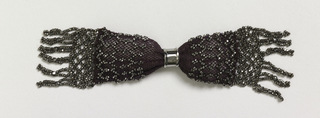 Crocheted purple silk ornamented with cut steel beads in lattice pattern; linked steel beads and fringe at each end; one simple steel ring controls side closing.