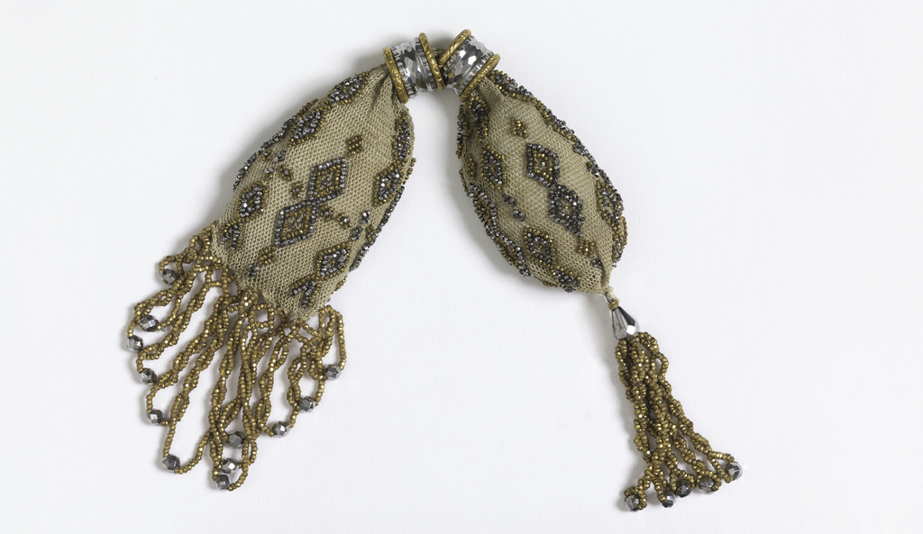 White silk purse ornamented with cut steel and gold beads in small diamond pattern. Two rings of cut steel in gold control side opening. Twisted gold beads ending in larger cut steel beads form fringe on one end, a tassel on the other.