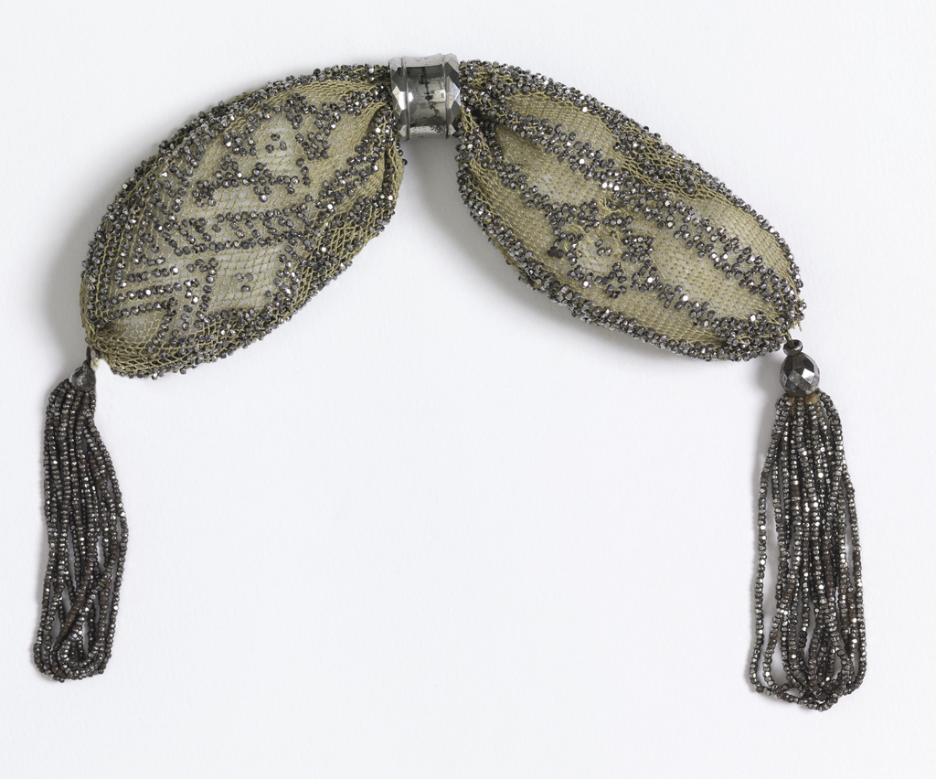 White silk purse ornamented with cut steel beads in bar and hexagonal pattern on one side, zigzag and diamond pattern on the other. One steel ring controls side opening; tassels of small steel beads at each end.