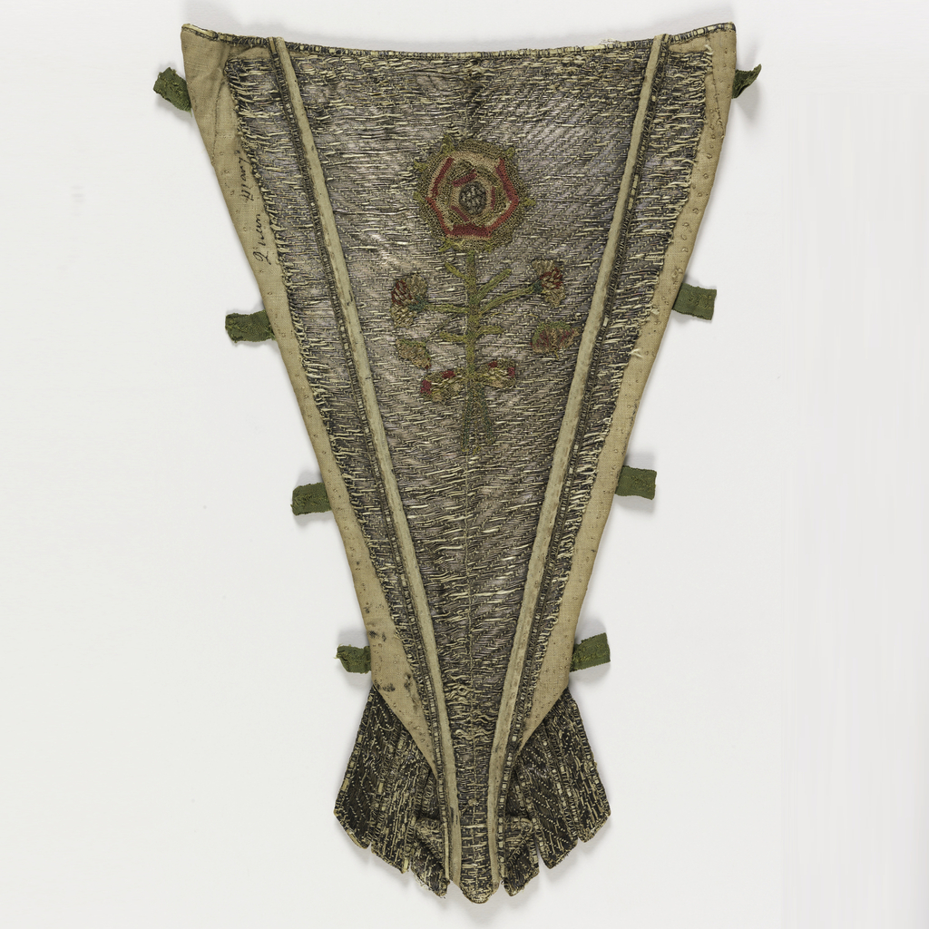 "Stomacher with a slightly u-shaped upper edge; the bottom finishes in a point with three independent tabs on either side. The front is linen, almost entirely covered with couched silver metallic yarns; while the metallic yarns are laid on horizontally, the couching stitches follow a ""V"" pattern. In the center is a single rose tied with a bow. The rose was made separately from red and green silk and gold metallic yarn in a needle lace technique; it is sewn on top of the silver couching.  The center panel is trimmed with white silk piping and a narrow woven metal ribbon; eight green silk tabs project from the sides for pinning the stomacher in place. Stiffened with ribs of an unidentified material, and lined with block printed linen with a pattern of small birds in a scrolling vine in red on white."