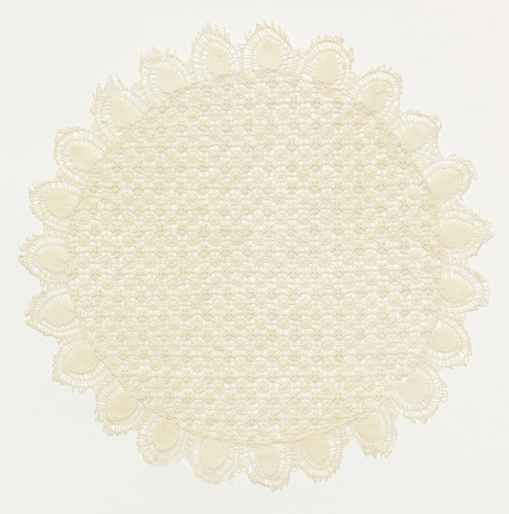 Small white mat with open, lacy pattern.