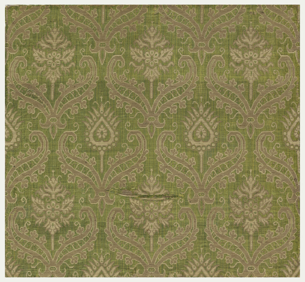 Beige and white floral forms in half-drop arrangement on green background.
