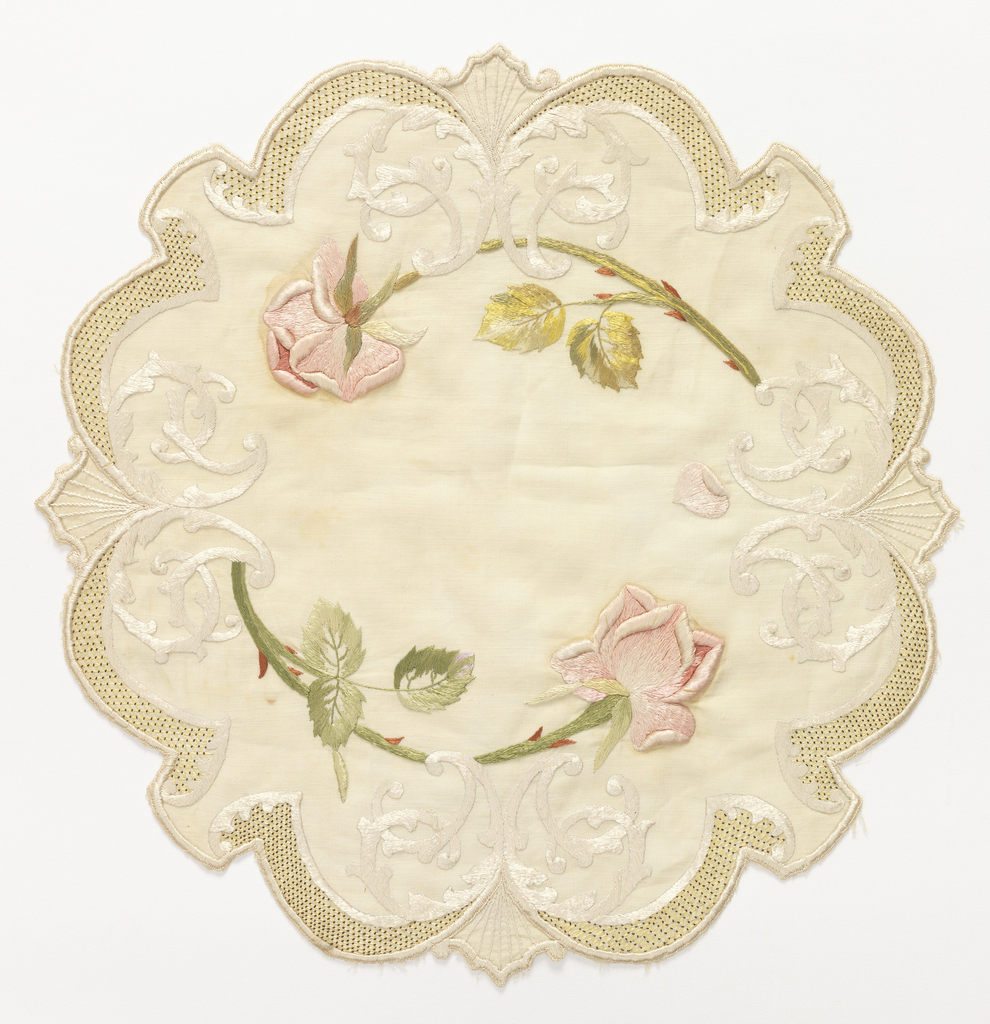 Table mat of off-white linen, approximately round with scalloped edges. Embroidered in pale greens, pinks, red and off-white silks with a cipher entwined with two pink roses. Border of  small yellow lattice with red dots.
