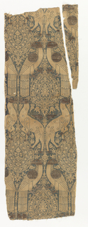 Fragment of woven silk with a teardrop-shaped motif, filled with small flowering vine, flanked by confronted eagles and addorsed gazelles. In blue and tan with silver metallic.