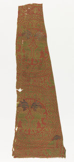Woven silk textile fragment with tangent roundels containing regardant griffins, with a border of stylized floral motifs and symmetrical interlaced stems. In green on rust ground, silver gilt heads brocaded.