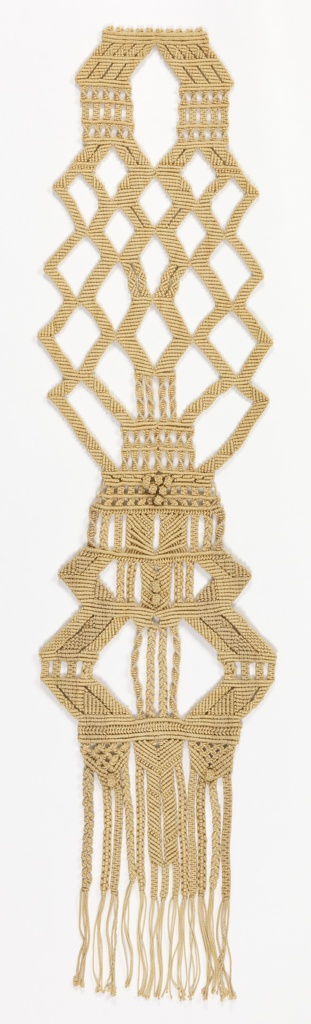 Long, narrow macrame hanging in natural linen, with diagonal work, twisted bands, and long fringes at the bottom.