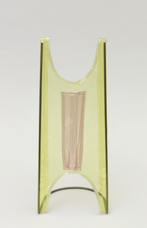 Rectangular vase with cutout arches on top and bottom; supported by black metal stitched into yellow vinyl body. Center has pink pocket for flower.