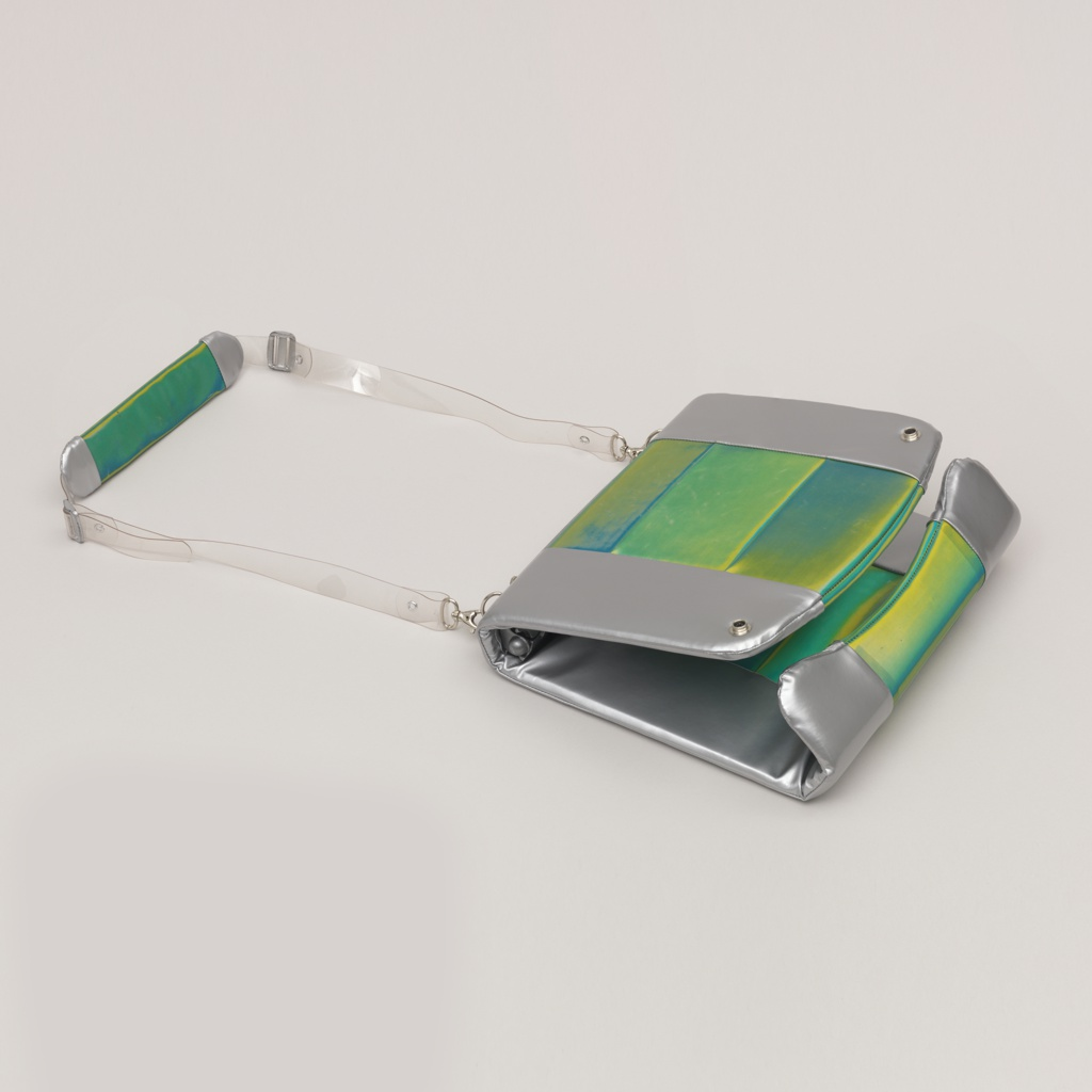"Rectangular silver and blue-green padded vinyl case (-1a) with shoulder strap on one side, flap at opposite side.  Flap unsnaps allowing case to open in notebook-like fashion, revealing bracket along inner spine.  Bracket can be opened to accept flat rectangular ""packets"" (-1c/j) inserted in any quantity or combination, as pages in a book.  Rectangular translucent orange vinyl case (-1b) with metal strip of electronic ports along exterior spine, flap opposite.  Flap unsnaps allowing case to open in notebook-like fashion (-1b cannot hold ""packets"").  There are eight ""packets,"" including: screen (-1c), keyboard (-1d), motherboard (-1e), drive (-1f), battery (-1g), and three blanks (-1h/j)."