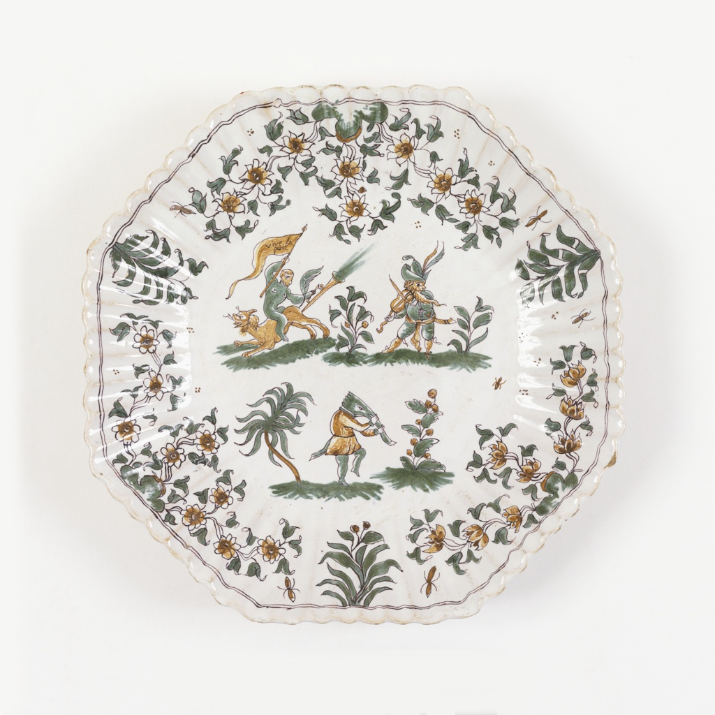 Octagonal form with fluted rim with narrow green border; center decorated with three Callot-style figures and foliage in green and ochre on white ground. One carries a flag with the words: Vive la paix.