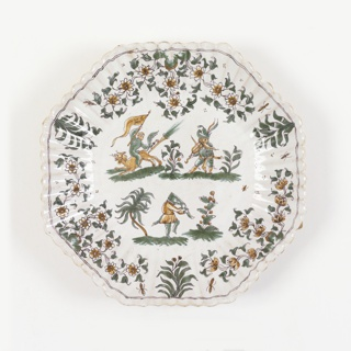 Octagonal form with fluted rim with narrow green border; center decorated with three Callot-style figures and foliage in green and ochre on white ground.