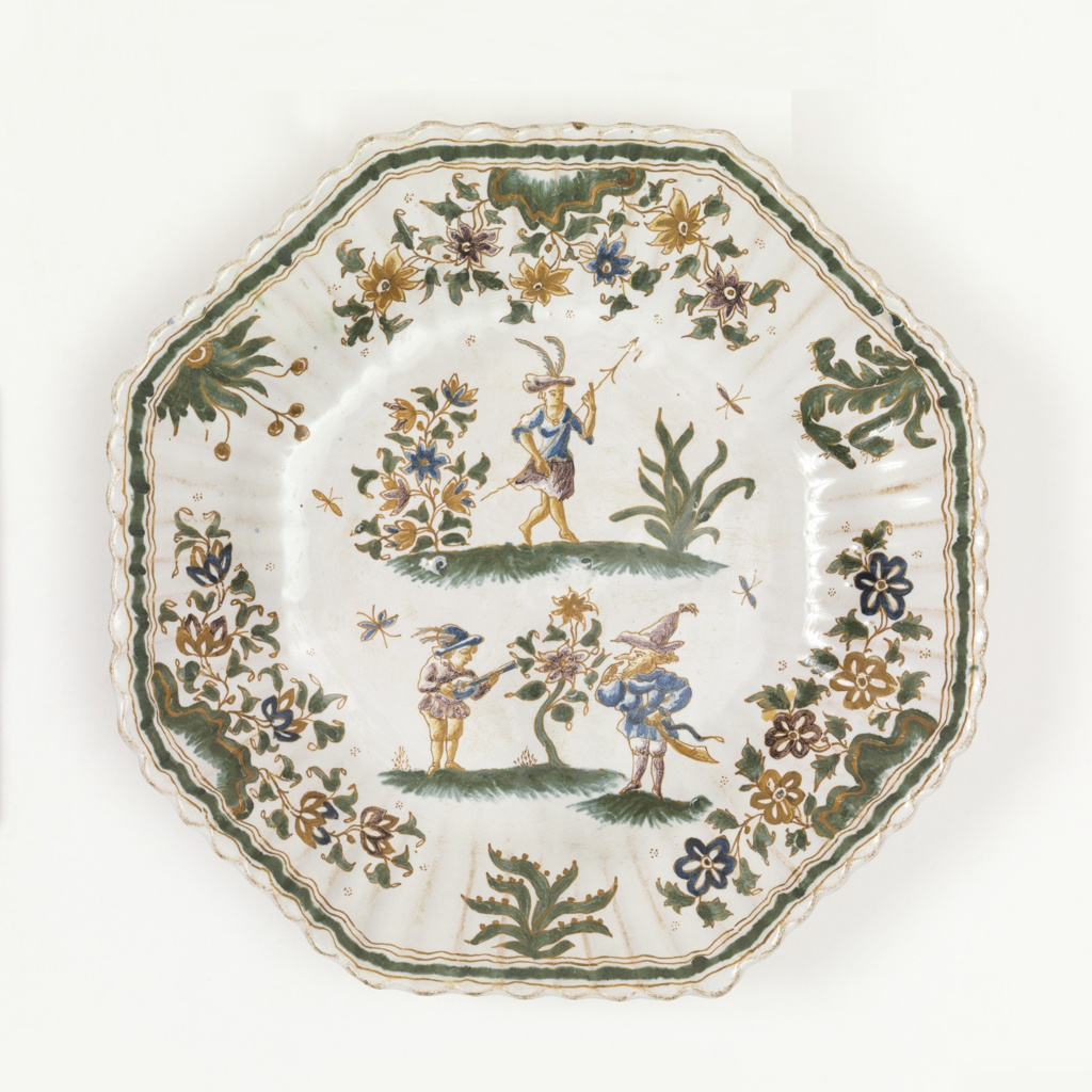 Octagonal form with fluted rim with thick dark green border; center decorated with three Callot-style figures and foliage in green and ochre on white ground.