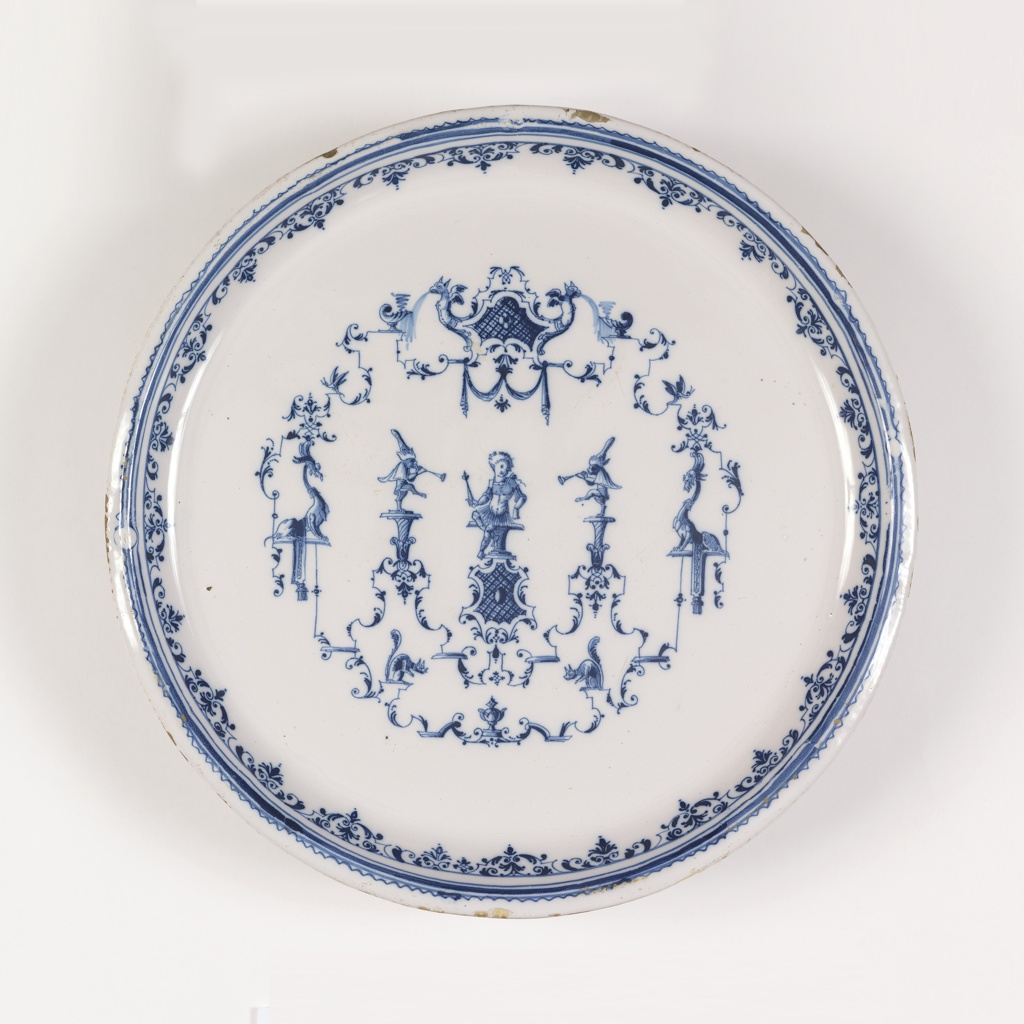 Circular form with blue and white grotesque decoration in the style of Jean Berain. Central figure is a seated youth dressed in classical garb, holding a scepter. Flanked by singeries and griffins. Below, two squirrels.