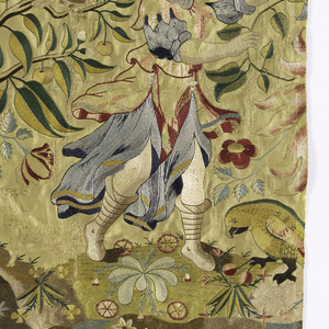 Panel of light yellow satin with polychrome silk embroidery. A fountain surmounted by a swag of red fabric is in the center, with a lion recumbent in a grotto below it. The fountain is flanked by fruit trees with owls in their branches, with climbing Tudor roses, and a man with a spotted dog reaching toward a branch. Small flowers are scattered over the background. Backed with tan linen.