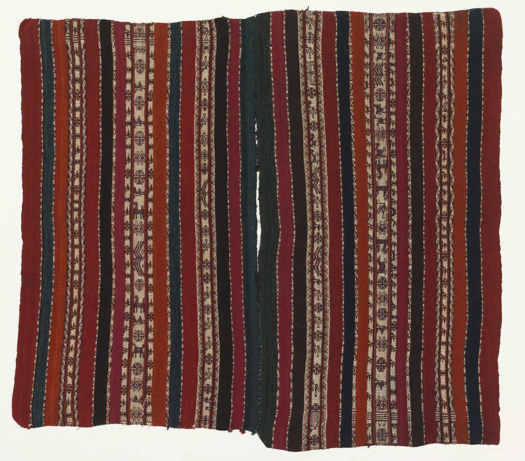 Small poncho, primarily in red, black and white, with patterned stripes showing small animals, flowers, birds and geometric shapes.