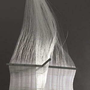 Form composed of four textile-like panels of loosly woven fiber optic strands depending from power source and X-form metal frame near top.
