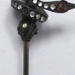 The head of pin represents a coiled snake with red eyes and body set with brilliants.