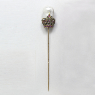 Straight pin surmounted by jeweled crown form surrounding large baroque pearl.