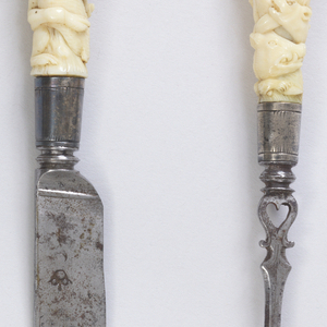 Three-tined fork, square shoulder, shaped stem with heart-shaped pierced hole, baluster neck. Silver ferrule with engraved borders. Ivory handle carved in deep relief with entwined hunting dogs and prey: roe, stag, rabbits, boar. Button cap at end of handle.