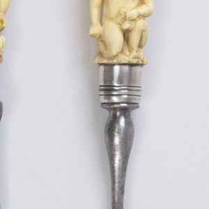 Two long pointed tines, curved shoulders and baluster-shaped neck. Plain silver ferrule. Ivory handle carved in deep relief; three putti, one of them kneeling on the ground, the other two climbing on his shoulders.