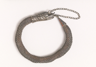 Bracelet of silver filigree with clasp representing a snake's head.