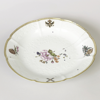 Circular form, with overglaze gilt and red border and Russian Imperial arms opposite the Imperial Order of St Andrew the first called, on the rim, the central well with underglaze moulded white floral pattern, and colorful Deutsche Blumen scattered over the whole surface.