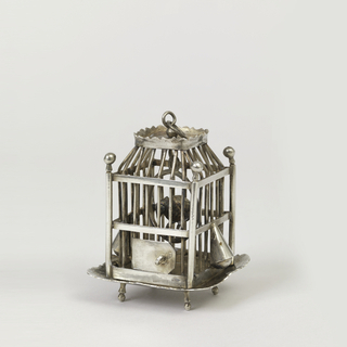 Four-footed scrolled tray supports barred cage between four finialed corner posts. Hinged false door. Scrolled cresting around top to which is fixed a ring handle. Contains parrot in ring perch. Dutch standard mark on base and door. Export mark on door.