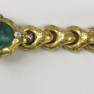 Cabochon emerald set into center and surrounded by bands set with diamonds, the links engraved with foliagein reserves. The bracelet in fitted box covered with velvet and with gold leaf crown impressed into textile.