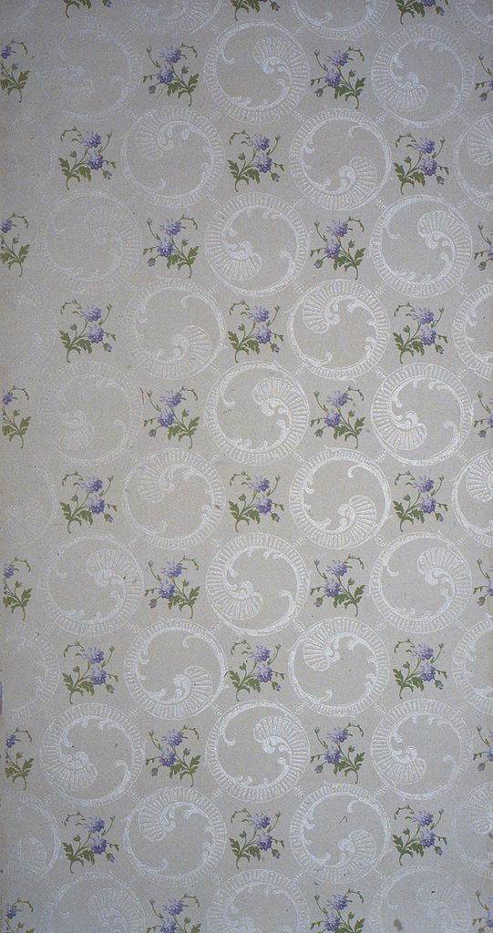 On lavender-gray ground, circular scroll motifs in white all over, with staggered stemmed purple flowers.