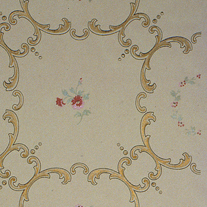 Gold scroll treillage containing floral wreaths and clusters of red flowers on light gray ground.