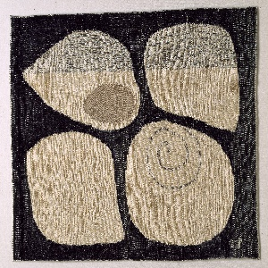 Four large, white curving shell shapes are inlaid in a dark grey weft satin ground by means of interlocking tapestry.  Within the shell shapes, texture and patterning are created by contrasting twill and satin weaves.