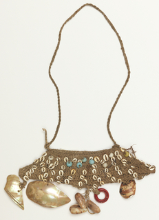 Flat, boat-shaped ornament like a shallow bag, with a long cord to hang around the wearer's neck and a flat piece of wood inserted in between front and back to hold the shape. Made of jute-like cord, decorated with small shells and seven colored beads; shells and one red plastic ring hang from lower edge.