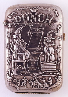 Rectangle with rounded top and bottom.  Front relief scene is of Punch seated and painting a dog wearing a ruffled collar.  Scroll between Punch and dog with writing.  Border with figures around Punch scene with a figure on a donkey on bottom. The figures on the side appear to be climbing.