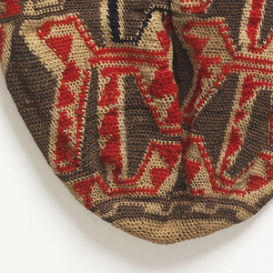 Round-bottom bag with an all-over geometric pattern with stepped details, in natural and brown plant fiber with red and purple wool. Long plaited strap, knotted once in the middle.